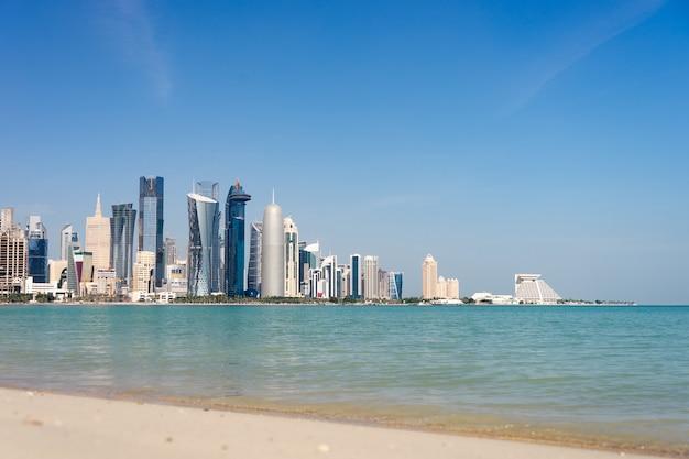 Вид на центр города с небоскребами с пляжа в дохе, катар.