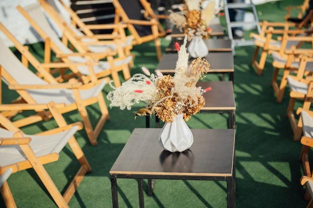 옥상에 야외에서 아늑한 카페의 전망. 나무 썬 라운저가 있는 테이블. 테이블에 말린 꽃이 있는 장식용 꽃병이 있습니다