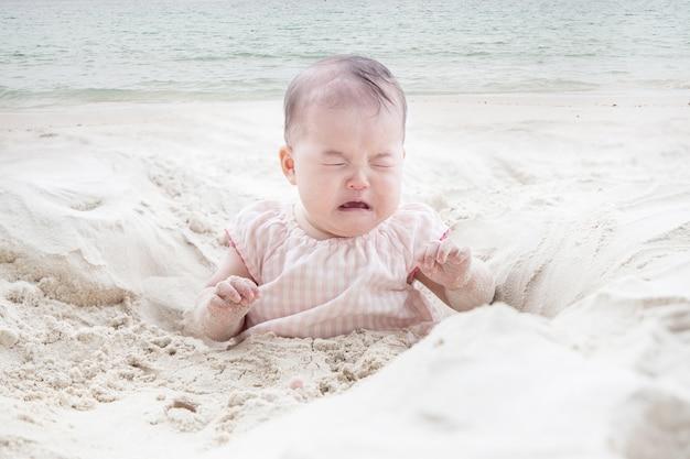 ビーチの砂で泣いている赤ちゃんのビュー