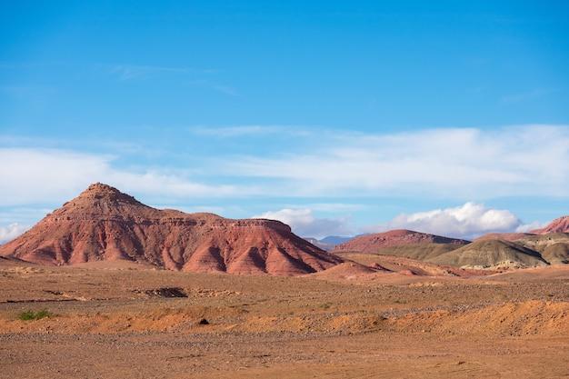 曇った青い空を背景に乾燥した風景と砂漠の山々の眺め
