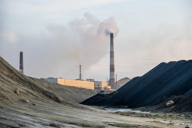 오염된 언덕과 흐린 하늘에 유독 가스를 배출하는 산업 공장 사이의 더러운 길과 큰 웅덩이 또는 강의 전망