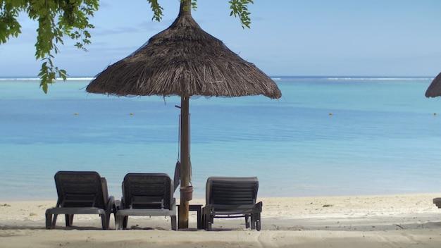 푸른 물 모리셔스 섬에 대한 기본 태양 우산 근처 빈 chaiselongue의 보기