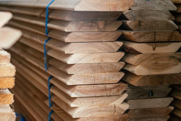 비스듬한 가장자리, 울타리 또는 클래딩 하우스 건설을 위한 플랑켄이 있는 쌓인 가장자리 낙엽송 보드의 끝 보기