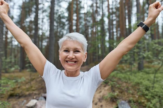 그녀는 자신의 기록을 깼을 때 성공에 기뻐하는 손을 올리는 정력적 인 자신감이 중간 나이 든 여자 주자의보기