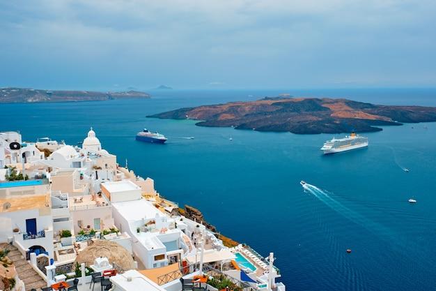Вид на город фира на острове санторини с круизными лайнерами в море