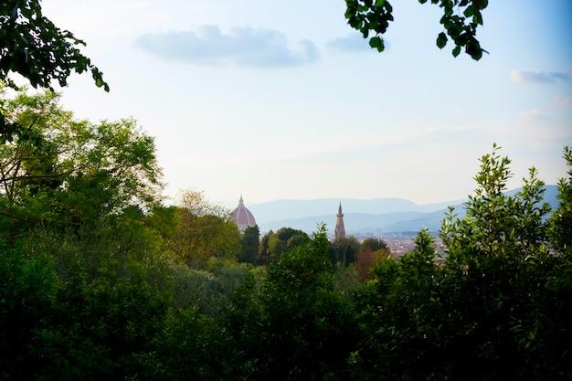 Взгляд города через зеленых деревьев, италии флоренса. летнее время duomo.