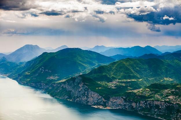 Вид на озеро гарда и окружающие горы с впечатляющими облаками.