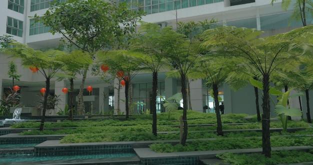 Вид на сад с фонтаном, водопадом и гирляндами на фоне здания современного делового города. куала лумпур, малайзия