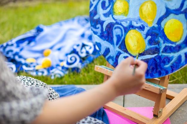 Вид руки молодой женщины, рисующей картину на домашней террасе