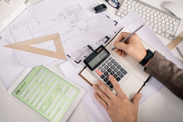 사무실에서 책상으로 작업하는 동안 펜과 계산기가 노트북에 메모를 작성하는 엔지니어의 손보기