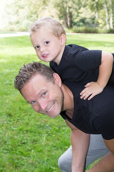 Взгляд счастливого маленького мальчика протягивая руки пока его отец нося его на плечах