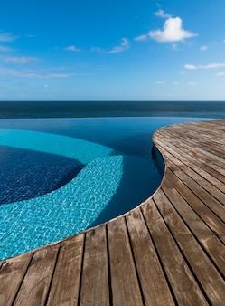 海と青空にインフィニティ プールの眺め。