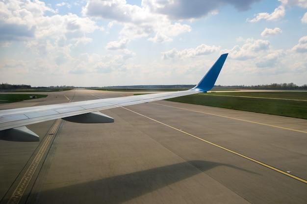 공항에 착륙한 후 활주로를 활주하는 제트 비행기 날개의 전망. 여행 및 항공 운송 개념입니다.