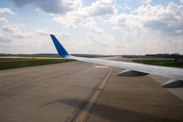 空港着陸後のジェット機の翼のタキシング滑走路の様子。旅行と航空輸送の概念。