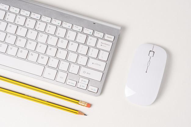 Вид клавиатуры и мыши современного компьютера с карандашами.