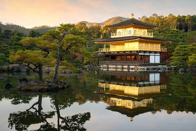 Взгляд kinkakuji известный золотой павильон с японским садом и пруд с драматическим небом вечера в сезоне осени на киото, японии.