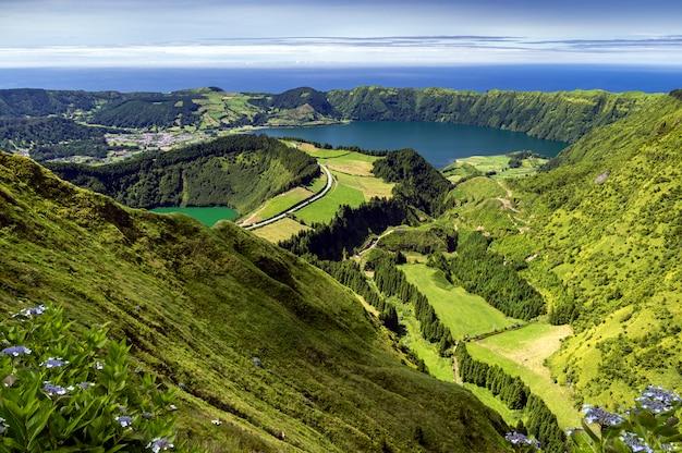 Вид на лагоа-де-сантьяго и лагоа-азул из зеленых гор в сан-мигель, азорские острова, португалия