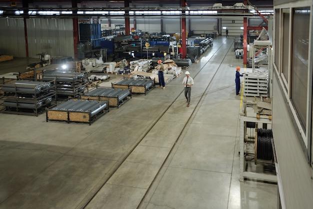 Вид на большой цех современного промышленного завода с группой инженеров, работающих с частями огромных машин автоматизации