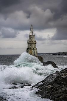 Вид на маяк в штормовую погоду на фоне темного неба