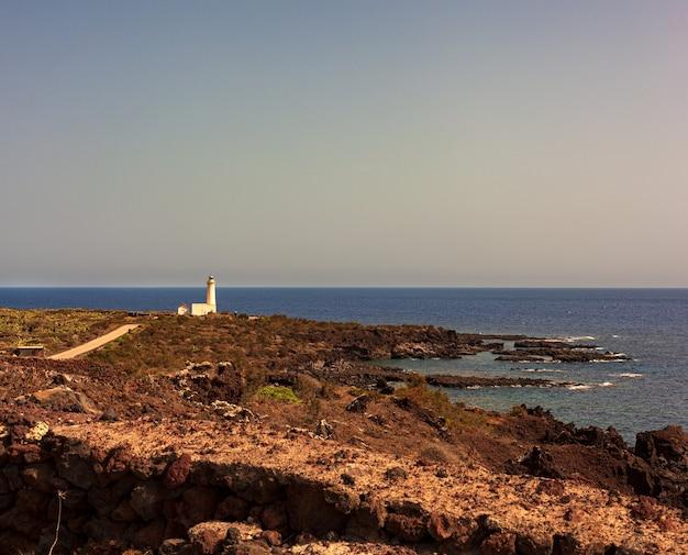 Вид на маяк в живописной скале из лавы, остров линоза. сицилия