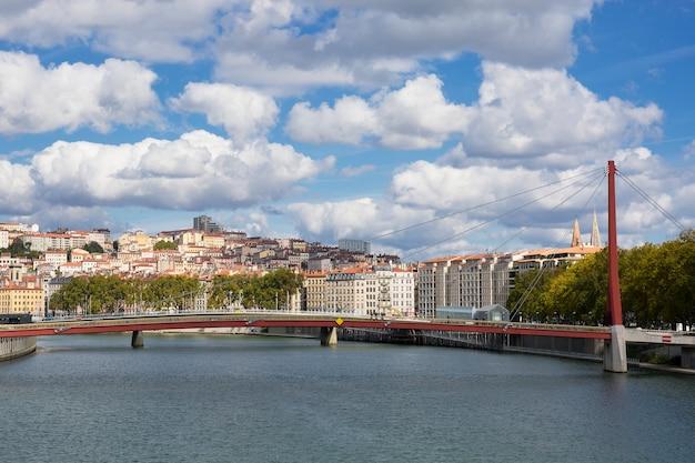 フランス、ソーヌ川に架かる赤い歩道橋のあるリヨンの眺め。