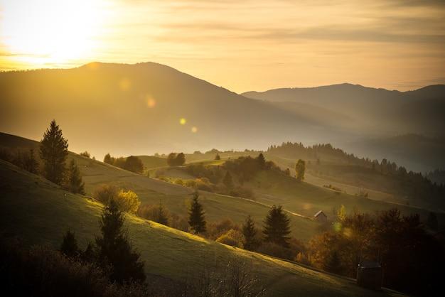 朝の谷と山の上の明るくカラフルな空と壮大な風景の眺め。なだらかな丘の上の草地に干し草の山がある農地の素晴らしい日の出。自然の概念。