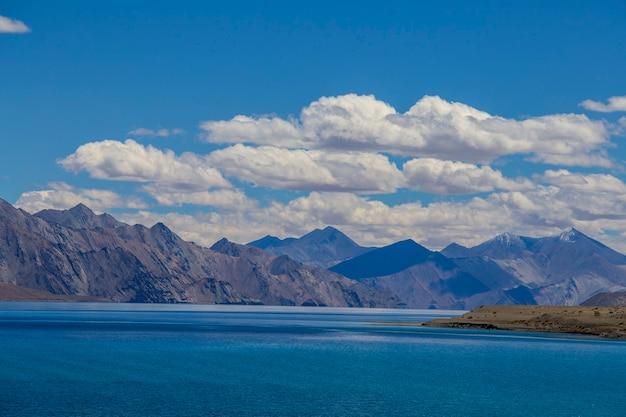 インドのヒマラヤ、ラダック地域、ジャンムー・カシミール州の青い空とパンゴン湖を背景にした雄大な岩山の眺め。自然と旅行のコンセプト