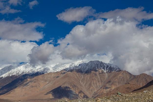 インド、ラダック地域、インドのヒマラヤの青い空と白い雲に対する雄大なロッキー山脈の眺め。自然と旅行のコンセプト