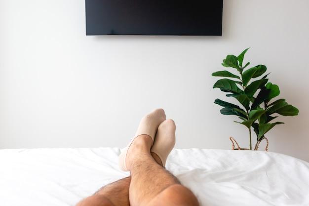 Tv와 식물이있는 흰색 침대에 남자의 다리보기. 휴식의 개념.