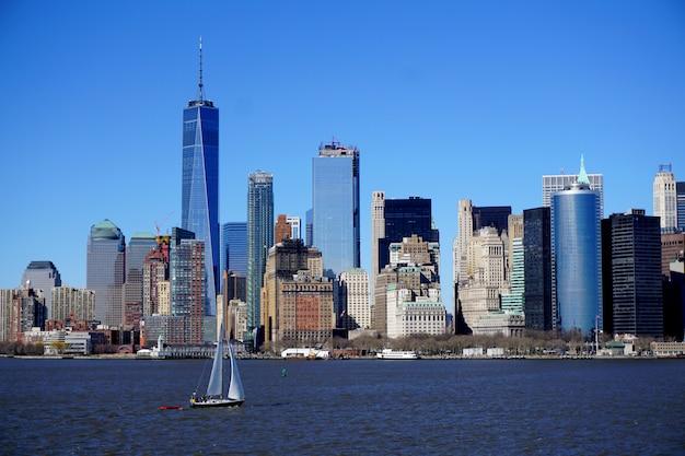 Вид на манхэттен, нью-йорк (сша), с моря. парусная лодка появляется на переднем плане