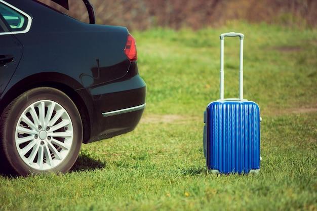 Вид на современный черный автомобиль и синий чемодан на берегу реки в солнечный день.