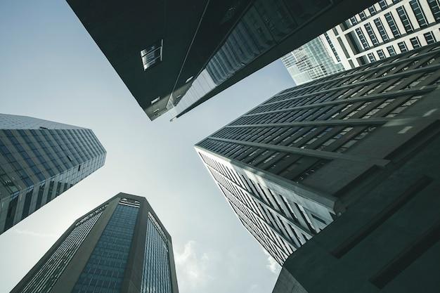 近代的なビジネスの高層ビルのガラスと空の中心街の商業ビルの風景を見る