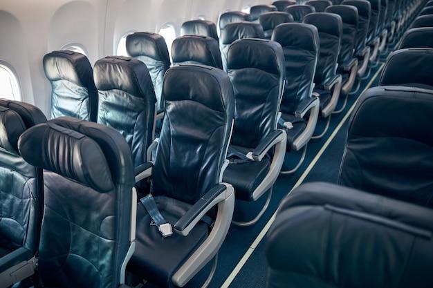 対称的に消える座席の列と青い座席のある飛行機のモダンなインテリアの眺め