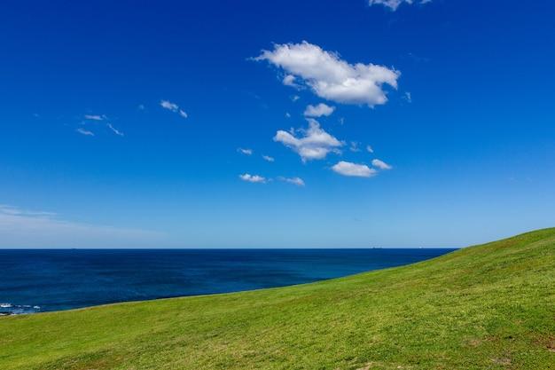 Вид на океан и красивый зеленый холм на белых облаках и фоне голубого неба.