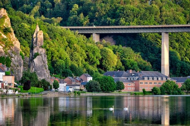 Вид на живописный город динант через реку маас. динан - это валлонский город и муниципалитет, расположенный на реке мёз.