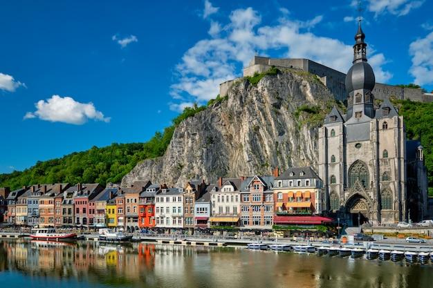 Вид на живописный город динан, цитадель динан и соборную церковь нотр-дам-де-динан через реку маас.