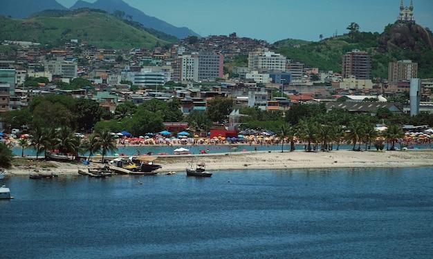 Вид на «писчинё де рамос» и несколько лодок в заливе гуанабара с церковью пенья и множеством гор на заднем плане. рио-де-жанейро, rj, бразилия. январь 2021 г.