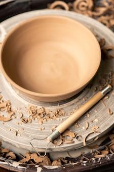 Вид гончарного круга с глиняной заготовкой и стружкой и ручным инструментом для обработки фаянса