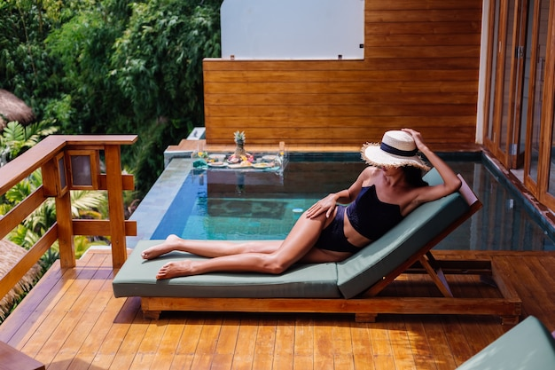 Вид на красивую загорелую бронзовую женщину с идеальной кожей в черном винтажном старом бикини лежит на зеленом солярии на удивительной вилле в солнечный день, отдыхая, наслаждаясь отпуском.