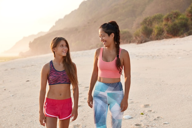 Вид симпатичных молодых гомосексуальных женщин, прогуливающихся по пляжу, дружеский разговор