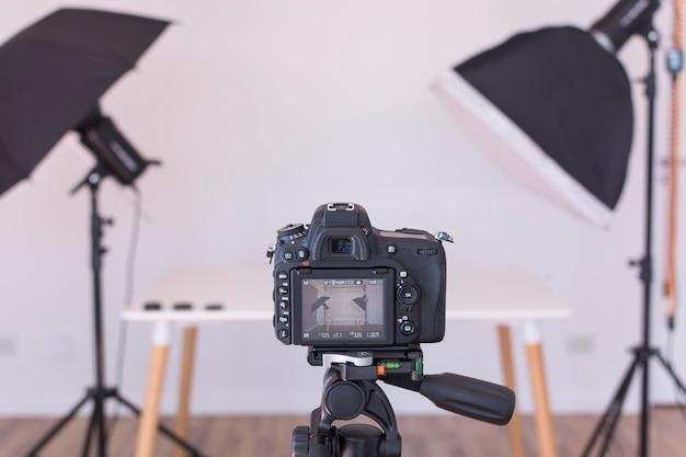 삼각대에 전문적인 현대 카메라 화면보기