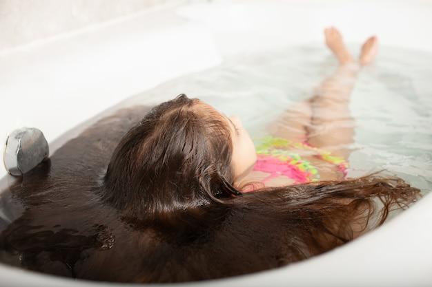 수영복을 입은 편안한 어린 소녀가 물에 펼쳐진 볼륨 있는 머리카락을 가진 인어공주를 보는 모습