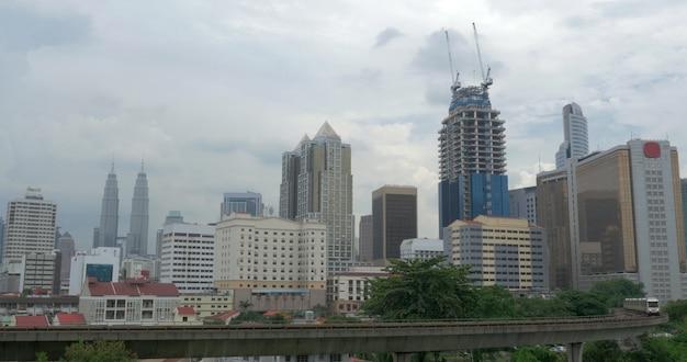 Вид на поезд на железных дорогах на переднем плане и небоскреб современных городских зданий на заднем плане. куала лумпур, малайзия