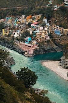 Вид на реки ганга и лакшмана с разноцветными домами столицы йоги ришикеша тонированное фото