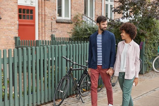 ロマンチックな異人種間のカップルの眺めは手をつないで、田舎の設定で歩きます