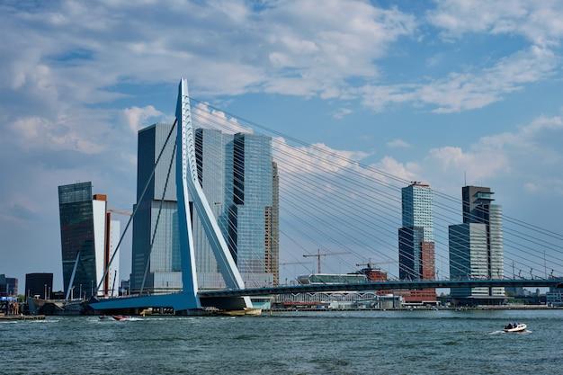 ニューウェマース川に架かるエラスムス橋と近代建築の高層ビルがあるロッテルダムの街並みの眺め。オランダ、ロッテルダム