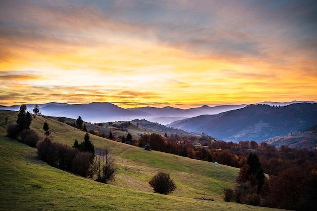 밝고 화려한 하늘과 산 마을의 아름다운 풍경보기