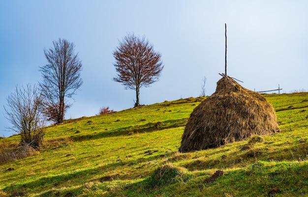 안개 산 위에 밝고 화려한 하늘과 아름 다운 풍경의 전망. 초원 언덕에 건초 더미와 안개 낀 아침 계곡에서 장엄한 일출. 자연의 개념.
