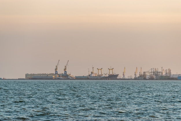 일몰 동안 크레인과 배송 바다 포트의 전망.