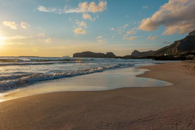 日没時に海辺の波と砂の景色